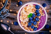 healthy smoothie bowl with granola, banana and fresh blueberries