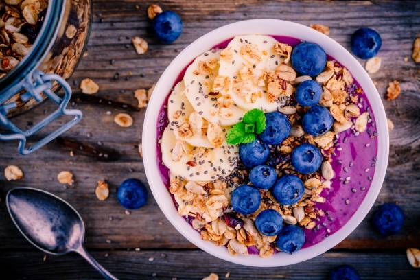 healthy smoothie bowl with granola, banana and fresh blueberries stock photo