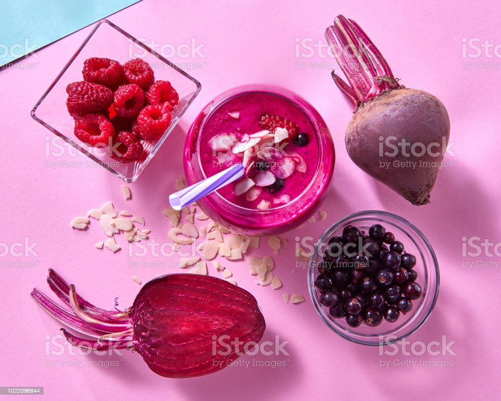 Healthy smoothies cooked from beets, raspberries, black currants and almond flakes on a duotone blue pink paper background. stock photo