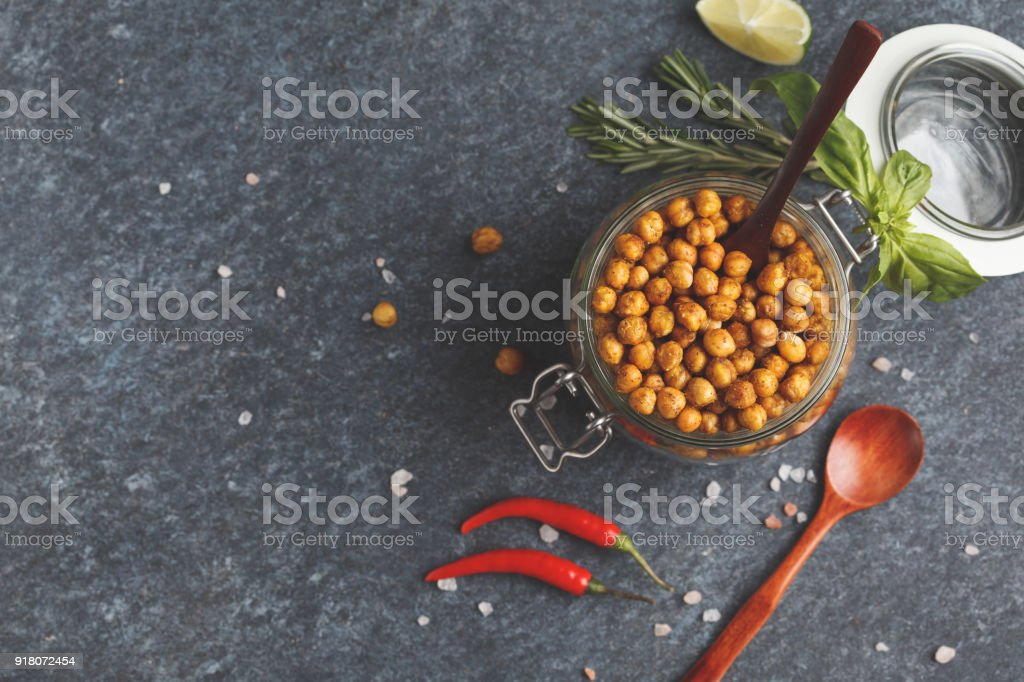 Healthy snack - baked spicy chickpeas in a glass jar, top view, copy space. Healthy vegan food concept. stock photo