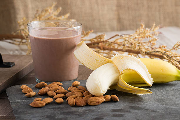 Healthy Snack-Banana Chocolate Milk Almonds Healthy Snack-Banana Chocolate Milk Almonds, great for after a workout, healthy breakfast, or quick and healthy snack chocolate milk stock pictures, royalty-free photos & images