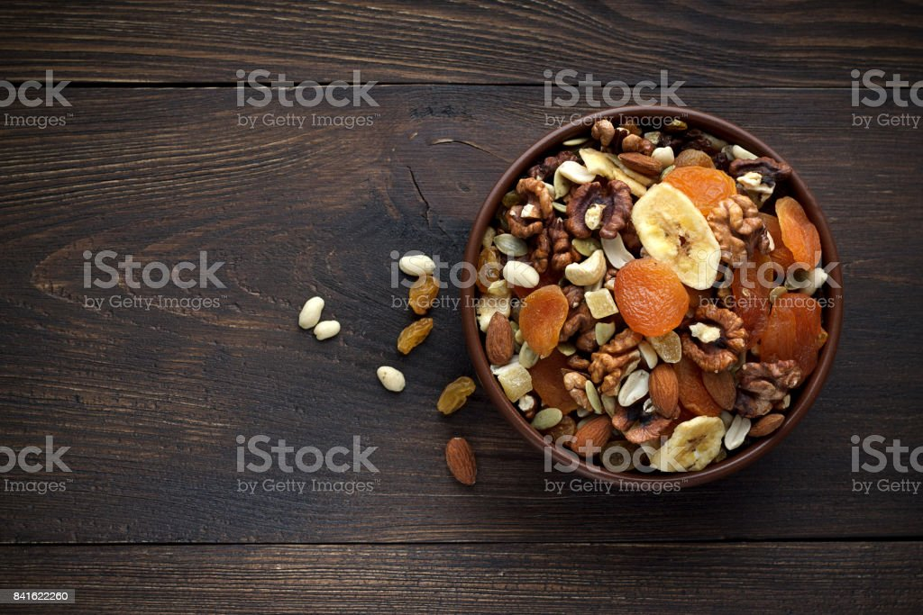 Healthy snacks in bowl on wooden background. stock photo