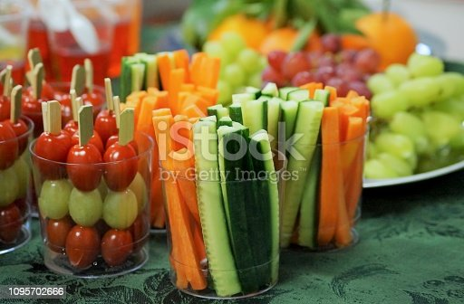 Snacks of fresh fruits and vegetables including carrots, cucumbers, tomatoes and grapes on a table at a children's party.