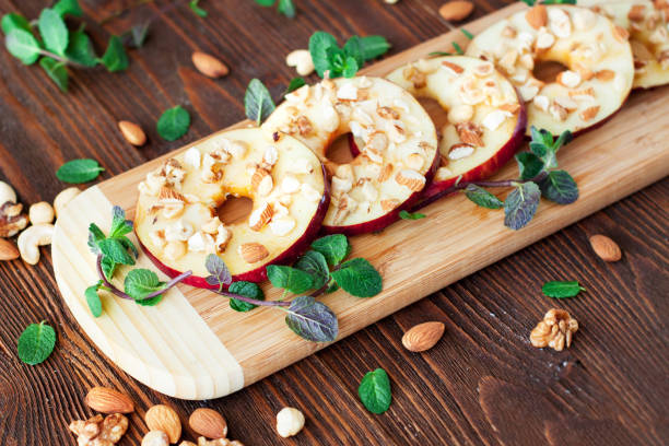 Healthy snacks sliced apples with honey and nuts stock photo