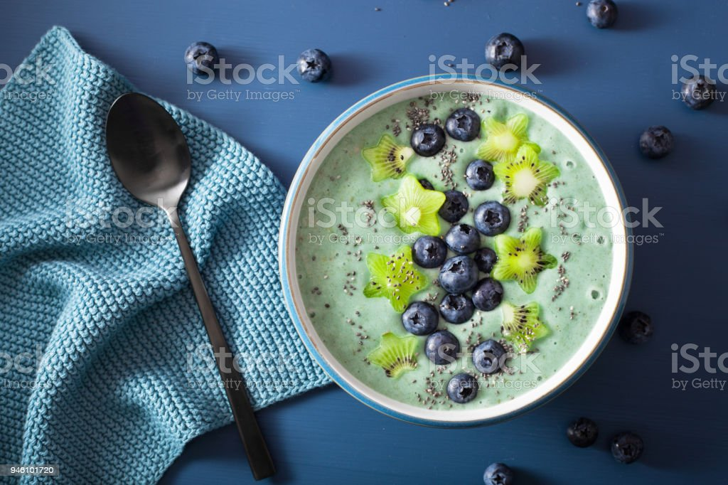 healthy spirulina smoothie bowl with blueberry, kiwi stars, chia seed stock photo