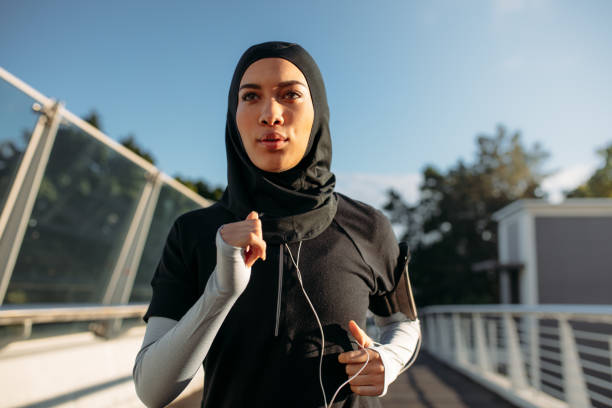 Healthy sporty woman in hijab jogging Healthy sporty woman wearing hijab jogging outdoors in the city. Islamic woman running early in the morning. modest clothing stock pictures, royalty-free photos & images