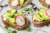 Healthy spring avocado toasts with radish, cottage cheese, pea sprouts and pepper for healthy diet breakfast. close up