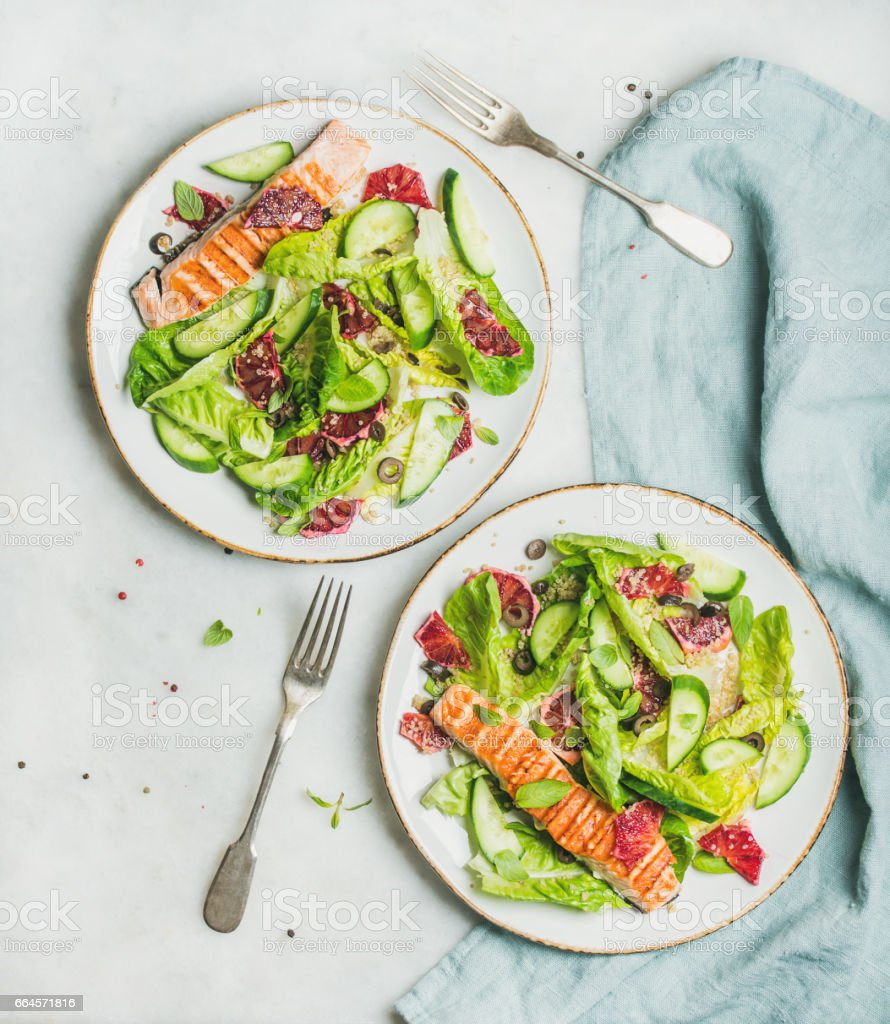 Healthy spring salad with grilled salmon, orange, olives and quinoa stock photo