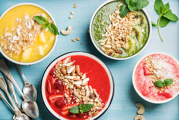 healthy summer breakfast concept. colorful fruit smoothie bowls on turquoise - oats food stock photos and pictures