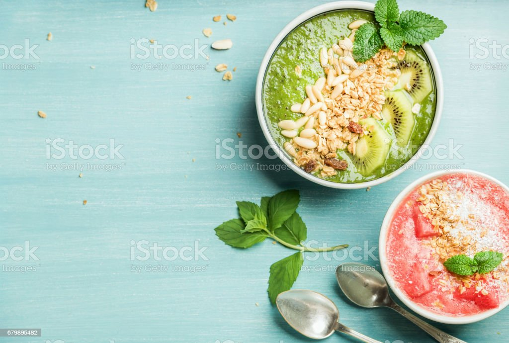Healthy summer breakfast concept. Colorful fruit smoothie bowls on turquoise blue background stock photo