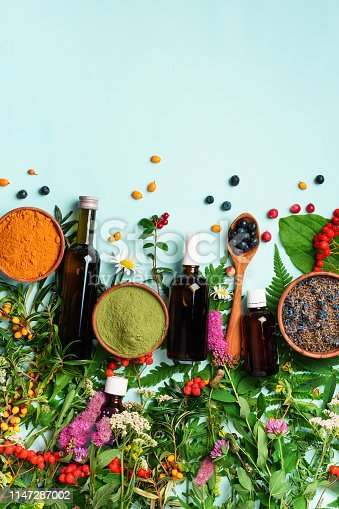 Healthy super food, berries, turmeric, spirulina, omega acid capsules, vitamin c supplement, medicinal herbs and spices on blue background. Antioxidants concept. Copy space, top view.