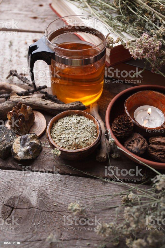 Saludable té en tetera de vidrio, hierbas secas, plantas y piedras en la mesa de madera. Homeopatía, alternativa, oculta el concepto de medicina ritual y hierbas, monocromo, vertical - foto de stock