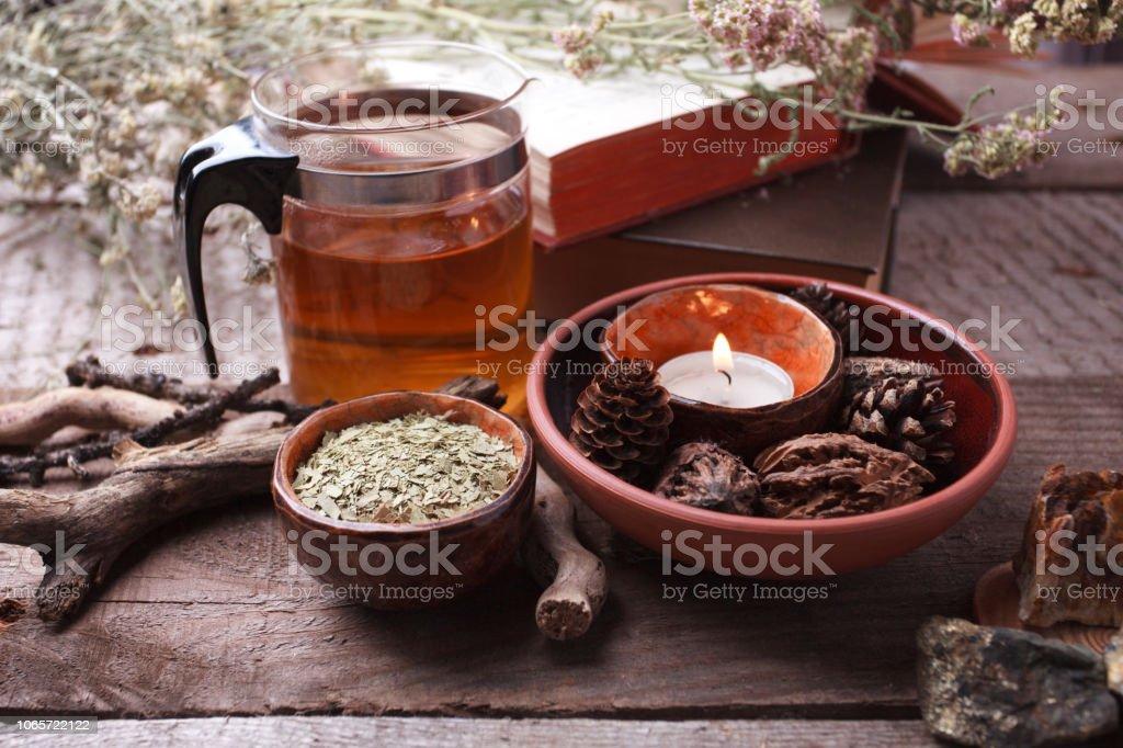 Saludable té en tetera de vidrio, hierbas secas, plantas y piedras en la mesa de madera. Homeopatía, alternativa, oculta el ritual y el concepto de la medicina herbaria, monocromo - foto de stock