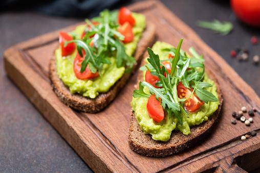 Healthy toast with avocado, tomato, arugula