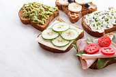 Toasts variations with avocado, ham, vegetables and dairy products.
