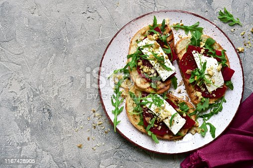 Healthy toasts with beetroot, feta cheese, nuts and arugula on a plate over grey slate, stone or concrete background.Top view with copy space.