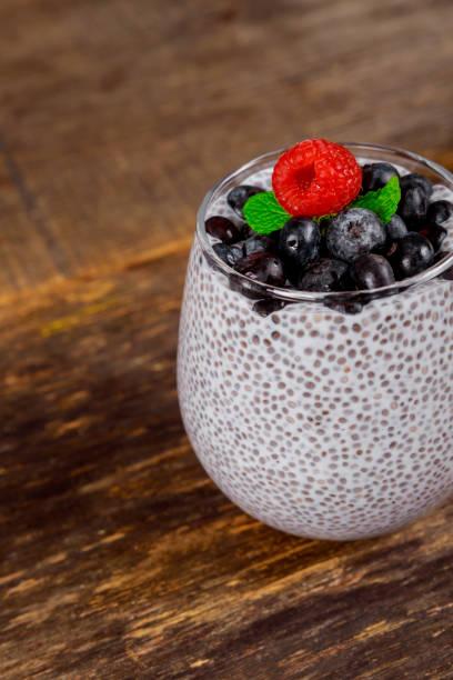 gesunde vanille chia pudding in einem glas mit frischen beeren - chia pudding kokosmilch stock-fotos und bilder