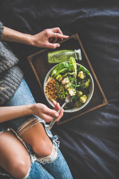 healthy vegan bowl and smoothie and woman eating, top view - kapustowate zdjęcia i obrazy z banku zdjęć