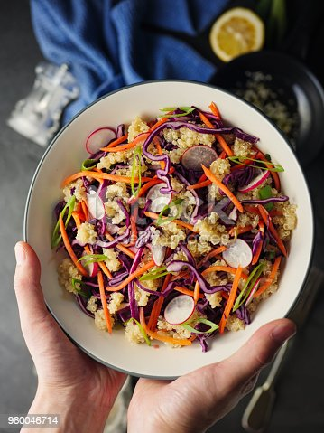 hand hold Home made freshness Asian style slaw shredded red cabbage, grated carrot, radish, spring with soy sesame dressing mix with quinoa.