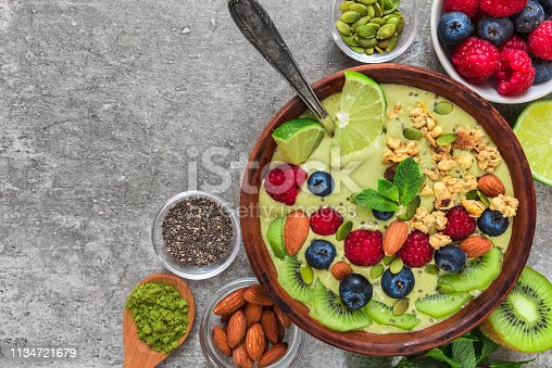 istock healthy vegan breakfast. matcha tea smoothie bowl with fruits, berries, nuts, granola and seeds with a spoon. top view 1134721679
