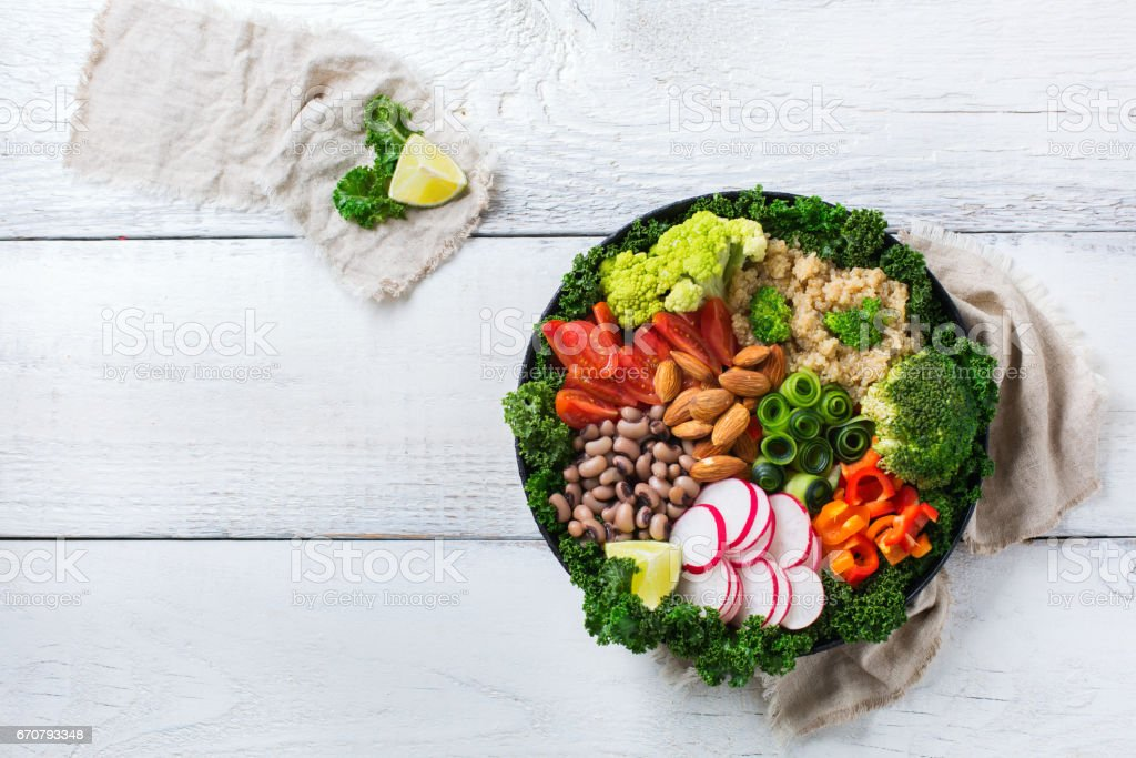 Healthy vegan buddha bowl with kale leaves and raw vegetables stock photo