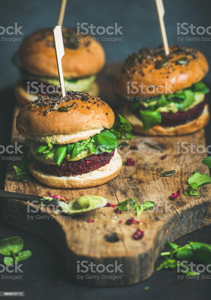 Healthy vegan burger with beetroot-quinoa patty, arugula on board stock photo