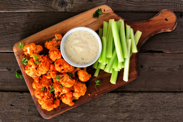 Healthy vegan cauliflower buffalo wings with celery and ranch dip, top view on a wood paddle board stock photo