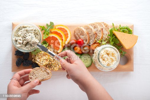 Personal perspective.  Vegan boursin, feta and cheddar cheese in recycled jars.  Raw fruit, berries, vegetables, whole grain bread and crackers on handmade reclaimed wood serving board.