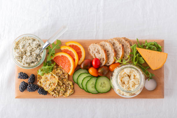 Healthy Vegan Cheese, Fruit, Vegetable, Crackers, Bread on Recycled Board stock photo