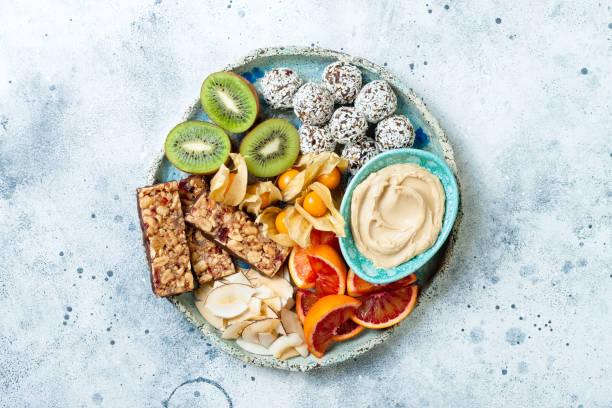 Gesunde vegane Dessert-Snacks-Eiweißgranola-Riegel, hausgemachte Rohenergiebälle, Cashewbutter, geröstete Kokosnuss-Chips, Kap Stachelbeere, Kiwi, Blutorange. Konzept der gesunden Süßigkeiten für Kinder. – Foto
