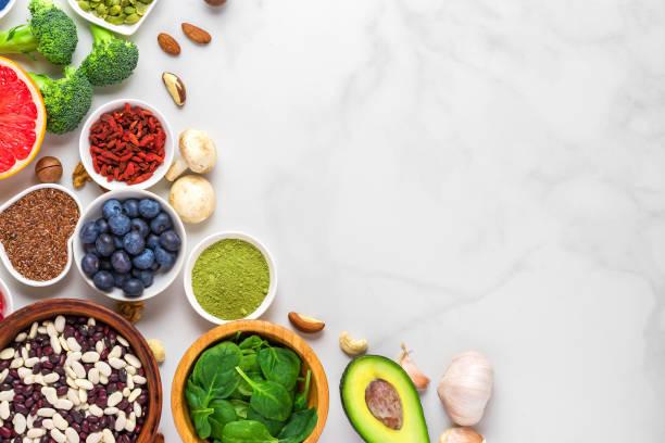 gezond veganistisch eten schoon eten selectie: fruit, groente, zaden, superfood, noten, bessen op witte marmeren achtergrond - spoorelement stockfoto's en -beelden