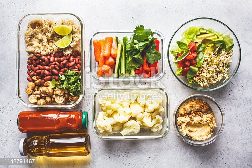 Healthy vegan food in glass containers, top view. Rice, beans, vegetables, hummus and juice for take-away lunch