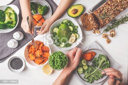 istock Healthy vegan food lunch, top view. Vegetarian dinner table, people eat healthy food. Salad, sweet potato, vegan cake, vegetables on white background. 1091749942