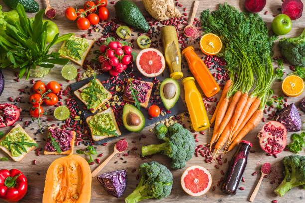 comida vegana saludable. bocadillos y verduras sobre fondo de madera. dieta de desintoxicación. diferentes coloridos zumos recién exprimidos. vista superior - vegana fotografías e imágenes de stock