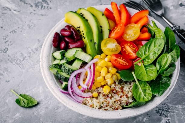 déjeuner végétarien sain bol bouddha. avocat, quinoa, tomate, concombre, haricots rouges, épinards, oignons rouges et salade de légumes paprika rouge. - saladier photos et images de collection