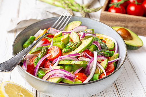 Healthy vegan meal, Juicy summer salad with blanched asparagus, cherry tomatoes, avocado slices and red onion, sprinkled with pepper and drizzled with olive oil and lemon juice on rustic wooden background