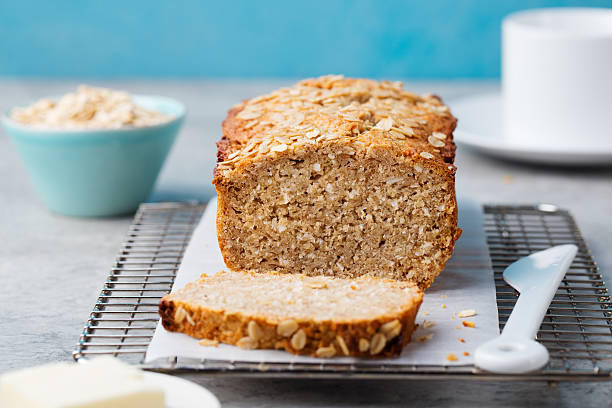 Healthy vegan oat, coconut loaf bread, cake on cooling rack Healthy vegan oat and coconut loaf bread, cake on a cooling rack Grey stone background wholegrain stock pictures, royalty-free photos & images