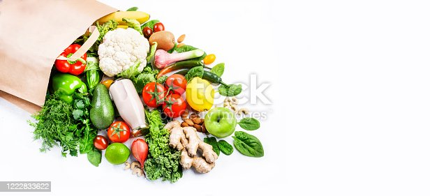 1126188273 istock photo Healthy vegan vegetarian food in full paper bag, vegetables and fruits on white background, copy space, banner. Shopping food supermarket, groceries and clean eating concept. Healthy food background 1222833622
