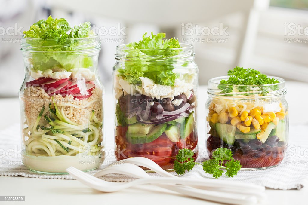 healthy vegetable cheese salad in mason jars stock photo