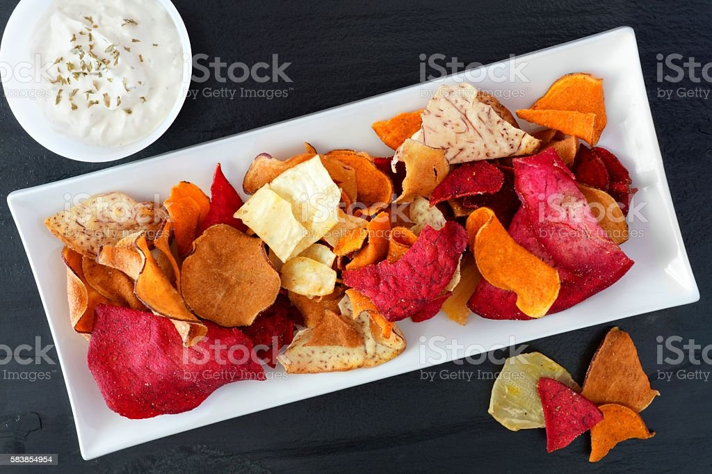 Healthy vegetable chips with dip, above view on slate stock photo