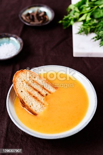 Healthy Vegetable Cream Soup in a bowl with toast grill on linen tablecloth. Vertical composition. Selective focus