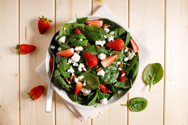 Gesunder Gemüsesalat aus frischem Spinat, Erdbeeren, Fetakäse und Mandel auf dem Teller. – Foto
