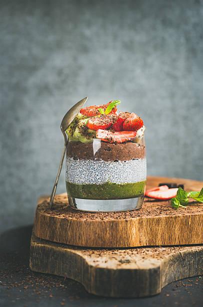 healthy vegetarian breakfast concept in glass over wooden board - chia samen pudding stock-fotos und bilder