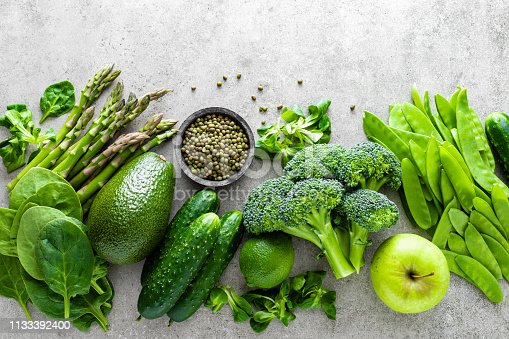 Healthy vegetarian food concept background, fresh green food selection for detox diet, raw broccoli, apple, cucumber, spinach, peas, asparagus, avocado, lime, corn salad and mung bean, view from above, flat lay
