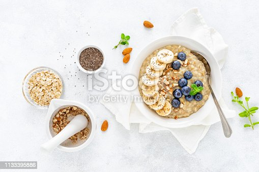 Healthy vegetarian food, oatmeal with fresh blueberry, banana, almond nuts and chia seeds for breakfast, view from above