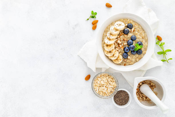 Healthy vegetarian food, oatmeal with fresh blueberry, banana, almond nuts and chia seeds for breakfast, view from above stock photo