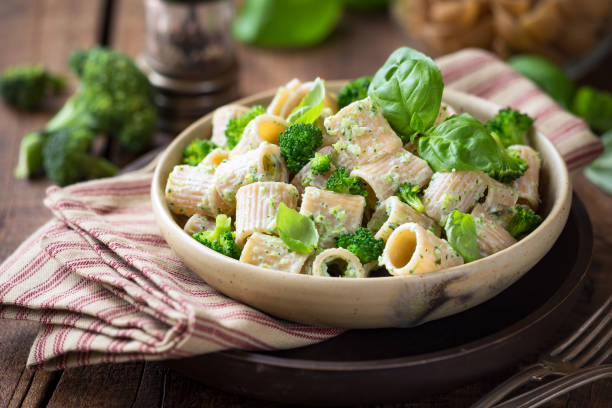 Healthy vegetarian pasta with broccoli and basil Vegetarian whole grain pasta with creamy broccoli sauce and basil rigatoni stock pictures, royalty-free photos & images