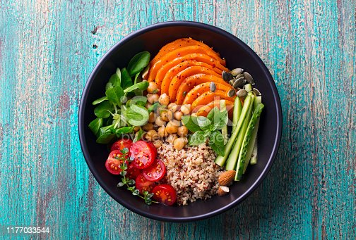 Healthy vegetarian salad. Roasted pumpkin, quinoa, tomatoes green salad. Buddha bowl. Blue wooden background. Top view