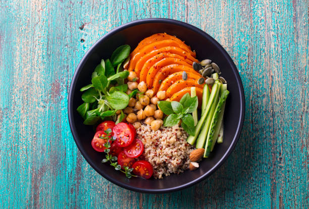 Healthy vegetarian salad. Roasted pumpkin, quinoa, tomatoes, green salad. Buddha bowl. Top view. stock photo
