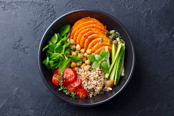Healthy vegetarian salad. Roasted pumpkin, quinoa, tomatoes, green salad. Buddha bowl. Slate background. Top view. stock photo